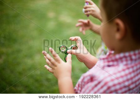 The little boy is spinning a spinner in his hand. Fidget spinner of the year. Green spinner. Blurred background.
