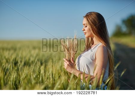 Beautiful happy woman girl smiling outdoors on green wheat field in summer nature. Pretty woman with natural makeup curly hairstyle in country village with green wheat. Attractive beauty girl in park