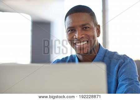 Portrait of a smiling young African businessman sitting confidently at his desk in a large modern office working on a laptop