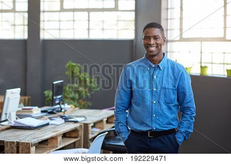Portrait of a confident young African businessman smiling while standing with his hands in his pockets in a large modern office