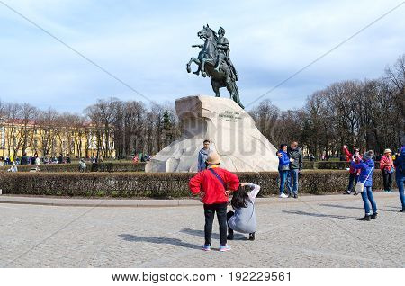 SAINT PETERSBURG RUSSIA - MAY 1 2017: Unknown tourists are photographed near monument to Peter the Great (Bronze Horseman) on Senate Square St. Petersburg Russia