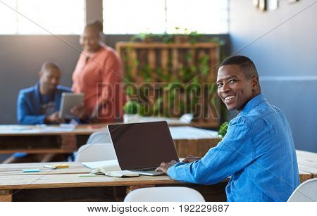 Portrait of a smiling young African businessman working on a laptop at a desk in a large modern office with colleagues working in the background