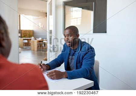 Focused young African businessman explaining business concepts and discussing paperwork while sitting with a colleague at a table in a modern office