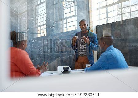 Focused young African businessman giving a presentation to work colleagues while standing in front of a chalkboard in a modern office