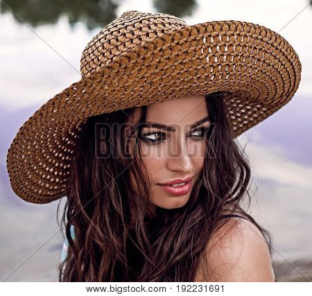 woman in big straw hat at sandy beach on a sunny day