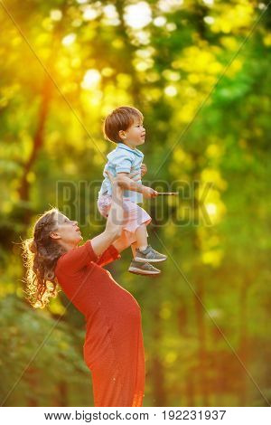 A pregnant woman in a red knitted dress high raises her son standing on the edge of the forest
