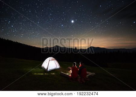 Night Camping. Silhouette Of Couple Tourists Sitting At A Campfire Near Illuminated Tent Under Starr