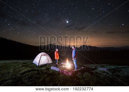 Night Camping. Couple Tourists Standing At A Campfire Near Illuminated Tent Under Night Starry Sky.