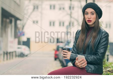 Urban girl holding a cellphone and coffee outdoors.