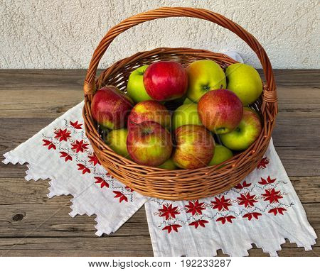 Basket with apples on a light tablecloth.