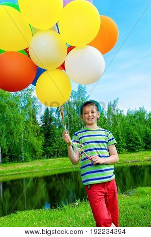 Happy boy enjoys with a sunny summer day and balloons. Summer holidays. Birthday.