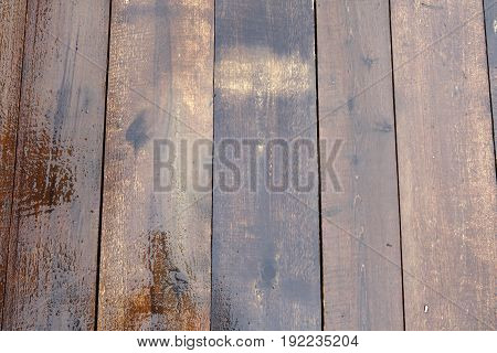 Planks of natural wood is wet after rain. Background of wood brown. The texture of the wet wood.