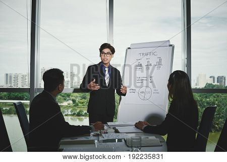 Handsome Vietnamese programmer presenting strategies on how to increase website traffic to his colleagues while having working meeting in spacious boardroom