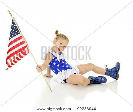 An adorable preschooler sitting on the ground in her patriot outfit, happily showing off her American flag.  On a white background.