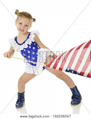 An adorable preschooler in a white star on blue outfit, happily waving an American flag.  Motion blur on flag pole and flag.  On a white background.