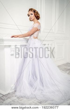 Charming bride woman in a beautiful wedding dress  with a lush skirt. Luxurious apartments.