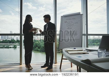 Profile view of confident Asian colleagues discussing joint project while standing at panoramic window in modern meeting room, picturesque cityscape on background