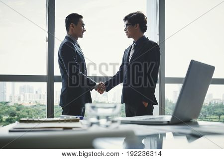Profile view of confident business partners shaking hands while standing at panoramic window of spacious boardroom