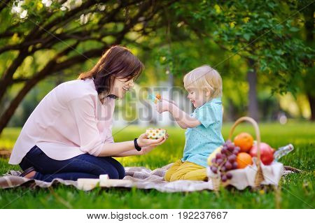 Cute little boy with his young mother opening nicely wrapped gift during picnic in sunny park. Summer birthday party concept