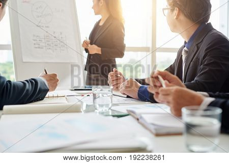 Young Asian speaker giving presentation while standing at marker board in spacious meeting room, her colleagues listening to her with interest and taking notes