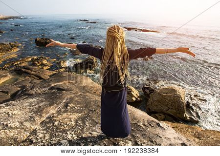 A young woman with blonde dreadlocks standing on the rocky shore of the ocean toward the sun. The view from the back.