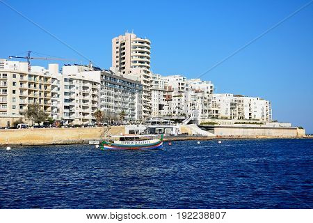 SLIEMA, MALTA - MARCH 30, 2017 - View along with waterfront with a tour boat in the foreground Sliema Malta Europe, March 30, 2017.