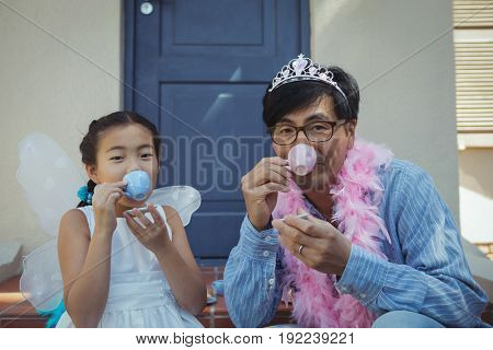 Portrait of father and daughter in fairy costume having a tea party at home