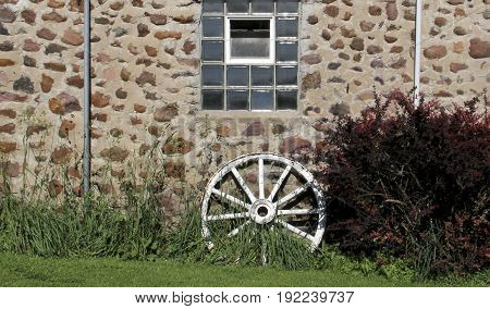 Field stone wall with wagon wheel makes a farming background