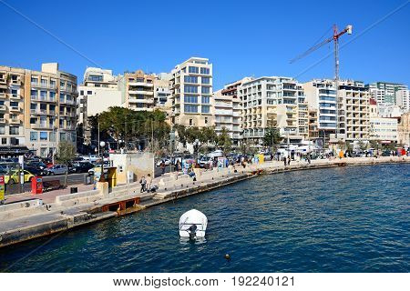 SLIEMA, MALTA - MARCH 30, 2017 - Tourists walking along the waterfront with a small boat in the foreground Sliema Malta Europe, March 30, 2017.