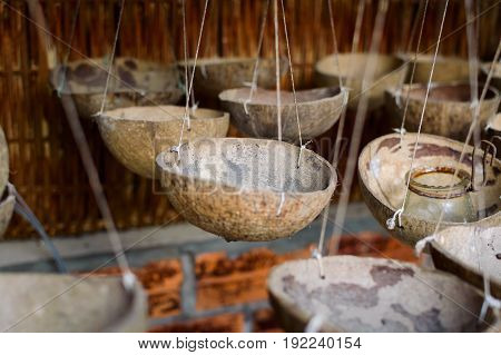 Lighting candles or capacities made of coconut shells suspended by rope