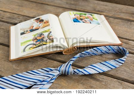 High angle view of photo album by necktie on wooden table