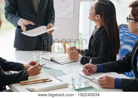 Productive teamwork in modern meeting room: Asian managers sitting at table and listening to their male colleague with interest while he presenting them his point of view on faced issue