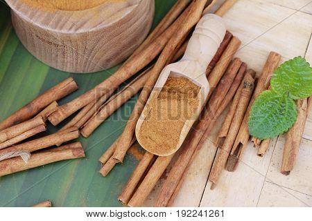 Cinnamon powder and sticks on wood background
