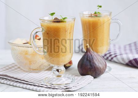 A delicious fresh melon and fig smoothie in a glass with a slice of fig on the white wooden background. Healthy food concept.
