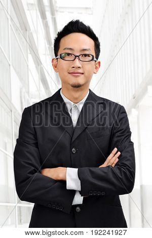 Asian businessman in full suit standing in front modern building.