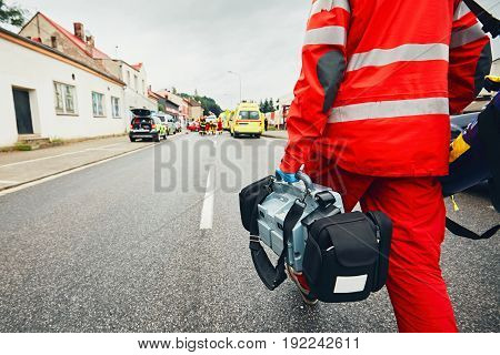 Hand of the doctor with defibrillator. Teams of the Emergency medical service are responding to an traffic accident.
