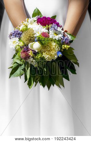 Woman/girl in white dress holding flowers at wedding/first holy communion.