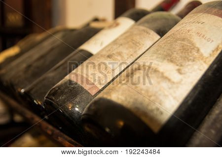 Old bottles of wine in old cellar closeup