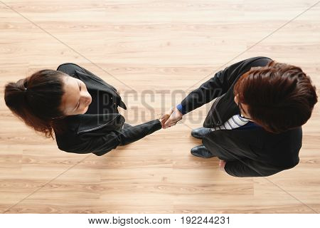 Confident business partners greeting each other with firm handshake while standing in office lobby, directly above view