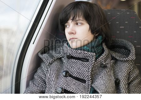 Girl in a coat looks out the window in the train