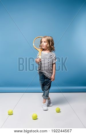 Beautiful Little Girl Standing With Tennis Raquet And Balls On Blue
