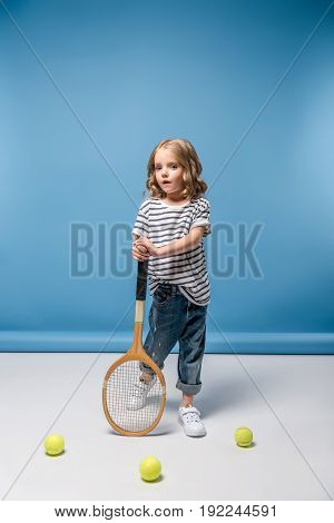Little Girl Standing With Tennis Raquet And Balls On Blue