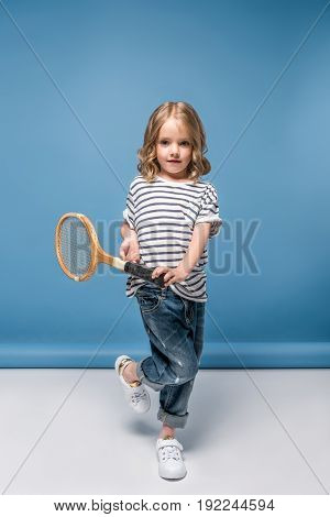 Sportive Little Girl Standing And Holding Tennis Raquet While Looking At Camera