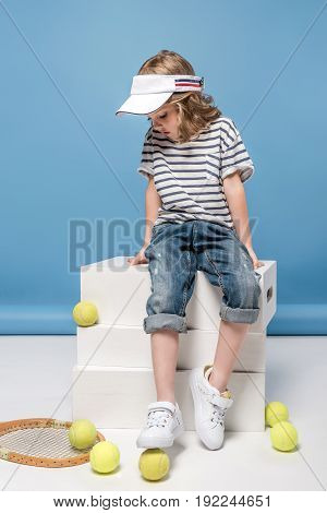 adorable little girl sitting on white boxes and looking at tennis raquet and balls