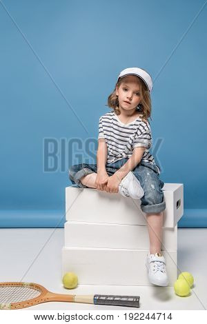 pretty little girl sitting on white boxes with tennis raquet and balls on floor