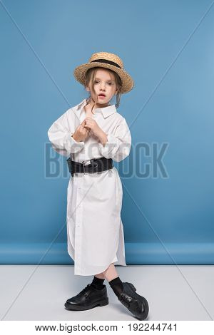 Stylish Little Girl Posing In White Shirt And Straw Boater, Studio Shot On Blue
