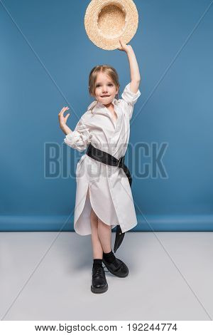 Adorable Little Girl Dancing In White Shirt And Holding Straw Boater, Studio Shot On Blue
