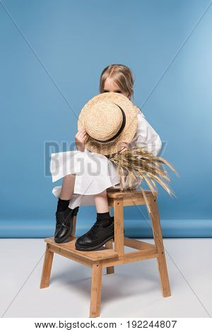 Shy Little Girl In White Dress Holding Wheat Ears And Straw Boater, Studio Shot On Blue