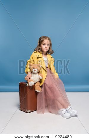 Beautiful Girl With Teddy Bear Sitting On Suitcase And Looking At Camera