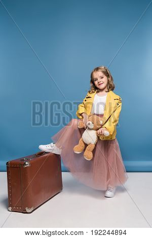 Adorable Little Girl Holding Teddy Bear And Posing With Suitcase In Studio